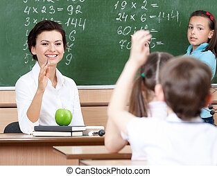 Beautiful teacher questions pupils at algebra