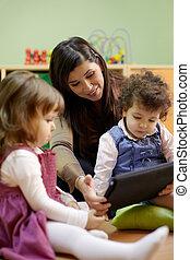 Teacher reading fairy tale to children at school - Caucasian...