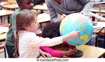 Teacher showing a globe to her pupils