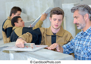 Teacher showing apprentice how to float cement