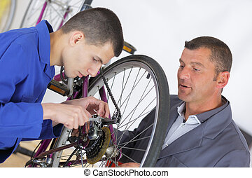 teacher showing aprentice how to fix a bike
