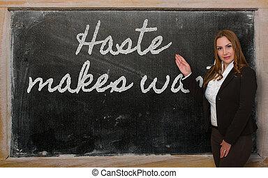 Teacher showing Haste makes waste on blackboard