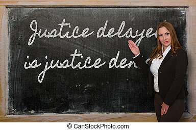 Teacher showing Justice delayed is justice denied on blackboard