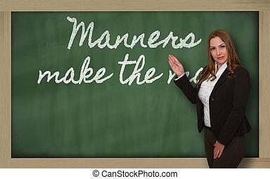 Teacher showing Manners make the man on blackboard