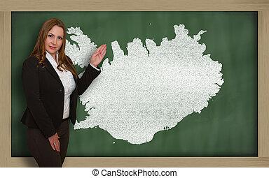 Teacher showing map of iceland on blackboard