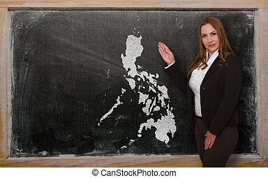 Teacher showing map of philippines on blackboard