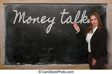 Teacher showing Money talks on blackboard - Successful,...