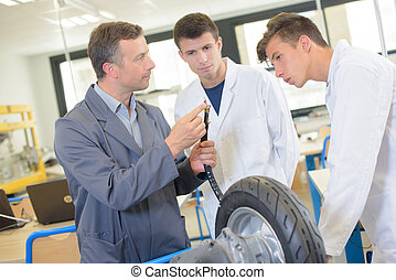 Teacher showing students the adapter for inflating tyre