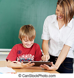 Teacher showing tablet to student - Teacher is showing...