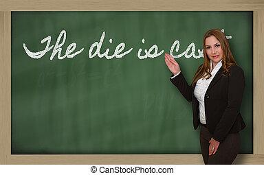 Teacher showing The die is cast on blackboard