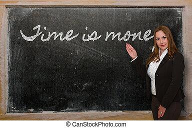 Teacher showing Time is money on blackboard