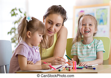 Teacher sitting at desk with two preschooler kids