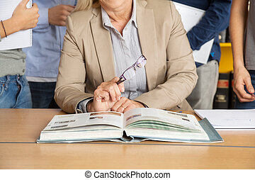 Teacher Sitting At Table With Students Standing In Background