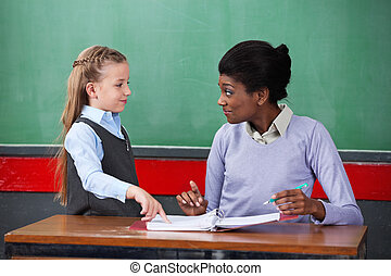 Teacher Smiling While Looking At Schoolgirl In Classroom