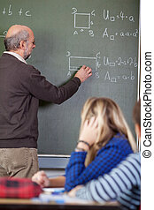Teacher Solving Sums On Blackboard With Students In...