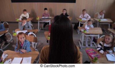 Teacher standing in front of pupils in classroom