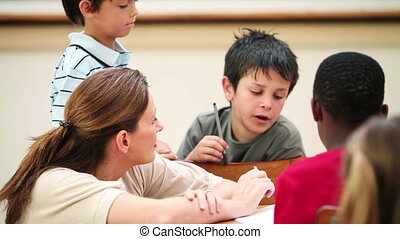 Teacher talking with her pupils in the classroom