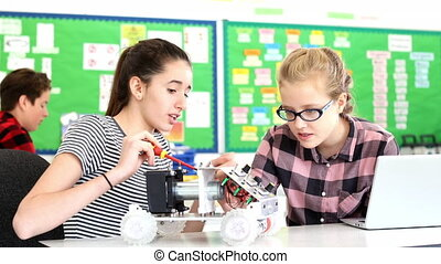 Teacher Talks To Pupils Building Robotic Car In Science Lesson
