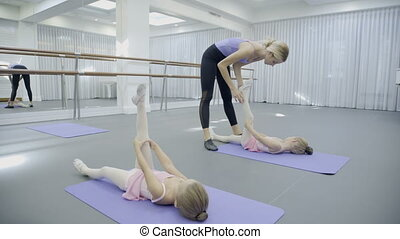 Teacher teaches little girls in ballet school. Attractive...