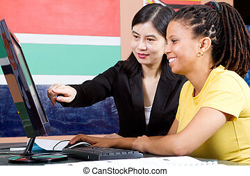 female chinese teacher teaching computer to adult african student