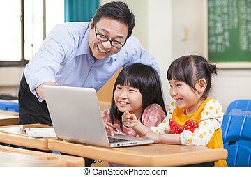 Teacher teaching  children with a laptop