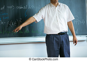 teacher teaching mathematics while pointing at blackboard