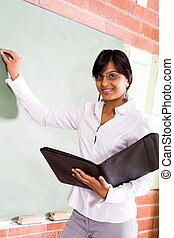 teacher teaching - teacher writing math sums on the board
