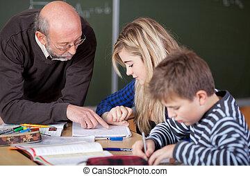 Teacher Teaching Student At Classroom Desk