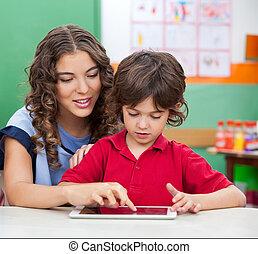 Teacher Teaching Students To Use Digital Tablet