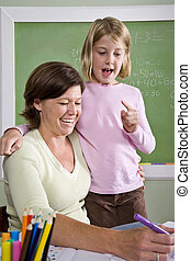 Teacher teaching young student in classroom