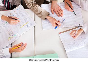 teacher tutoring students in classroom - overhead view of...