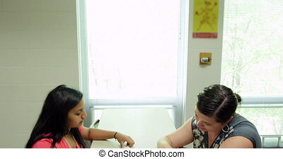 Teacher tutors a student in class.