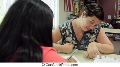 Teacher tutors a student in class. - High school teacher...