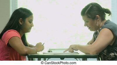 Teacher tutors a student in class.