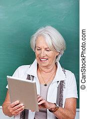 Teacher Using Digital Tablet Against Chalkboard