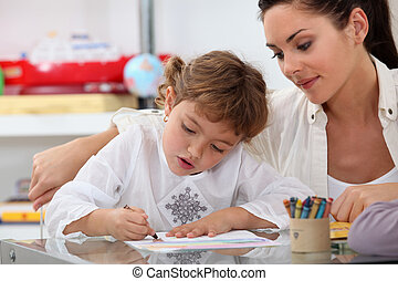 Teacher watching her pupil colouring a drawing