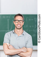 Teacher With Arms Crossed Standing In Classroom