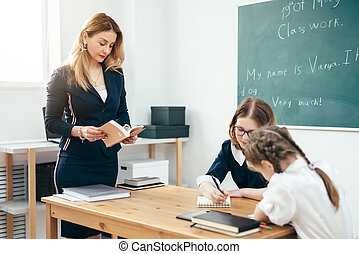 Teacher with book giving lesson in classroom.