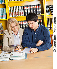 Teacher With Books Explaining Student In University Library