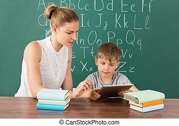 Teacher With Boy Using Digital Tablet In Classroom