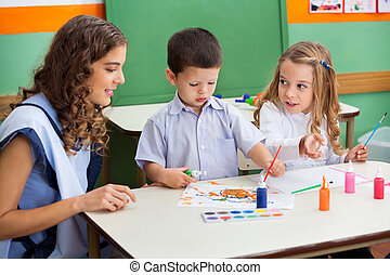 Teacher With Children Painting At Desk