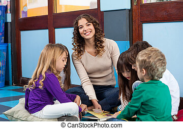 Teacher With Children Reading Book In Classroom