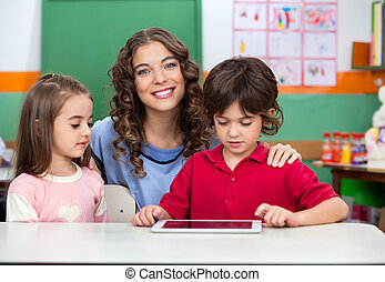 Teacher With Children Using Digital Tablet At Desk
