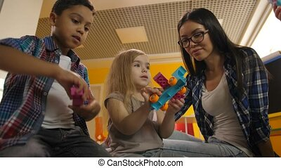 Teacher with diverse kids playing with didactic toys