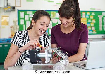 Teacher With Female Pupil Studying Robotics In Science Lesson