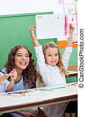 Teacher With Girl Showing Drawing At Desk