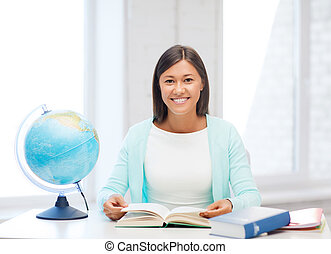 teacher with globe and book at school - education and...