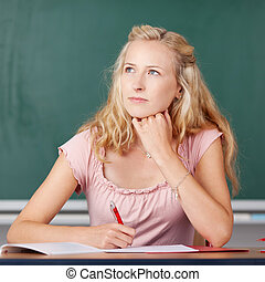 Teacher With Hand On Chin Looking Up At Classroom Desk
