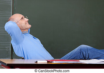 Teacher With Hands Behind Head Looking Up At Desk