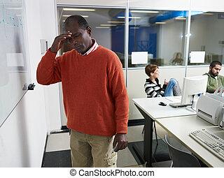Teacher with headache in computer lab